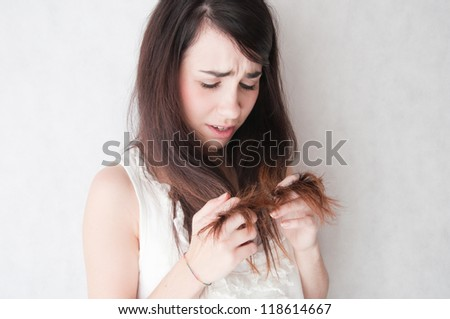 Problem with hair. Young woman worriedly looks at the tangled hair. - stock photo