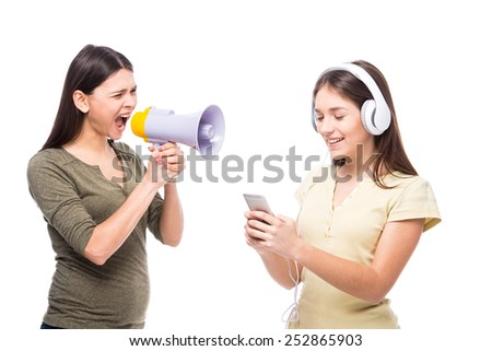 Problems between generations concept. Teen closed his ears with headphone while her mom yells at her. - stock photo