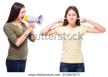 Problems between generations concept. Teen closed his ears with his hands while her mom yells at her. - stock photo