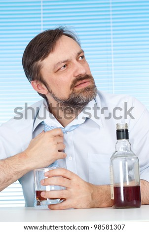 Problems business man sitting at a table with a bottle on a light background - stock photo