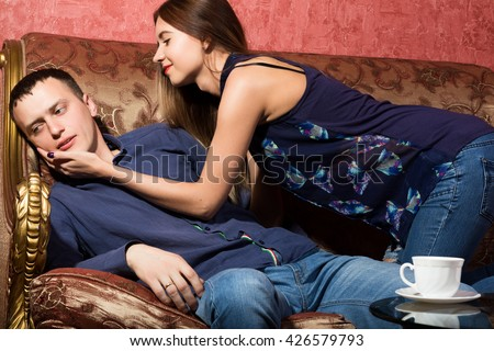 problems in family relationships, a young couple sitting on the couch. man hurt, he turned away from the woman - stock photo