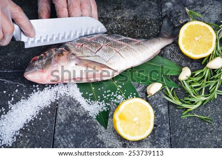 Process of cooking Dorado fish with lemon and herbs hands cook cut up the fish on a stone cutting board - stock photo