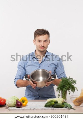 Process of cooking in the kitchen be chef in blue shirt. Handsome short-haired man showing pan, which he is going to use. - stock photo