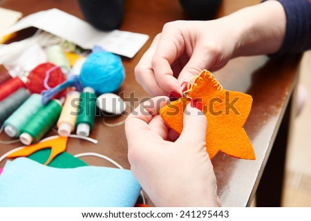 Process of hand made soft toys sewing with felt and needle for Christmas tree decoration - stock photo