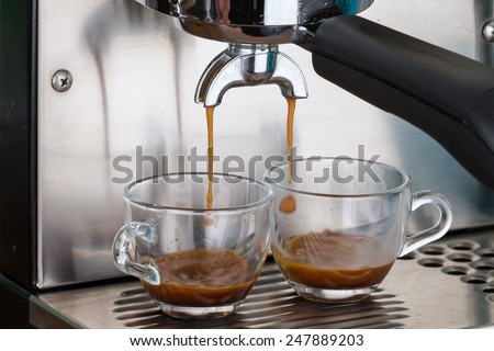 process of making two espresso shots using espresso machine - stock photo