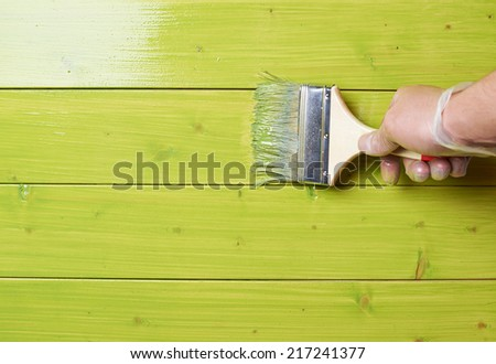 Process of painting the pine wood boards with the brush and the green paint - stock photo