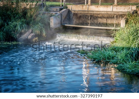 Processed and cleaned sewage flowing out from water reclamation facility to a river - stock photo