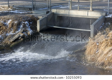 Processed and cleaned sewage flowing out of water reclamation facility, Fort Collins, Colorado; cold winter morning resulting in some steaming - stock photo