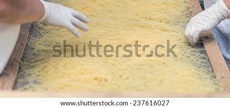 Processed pasta on machine tray at commercial kitchen  - stock photo