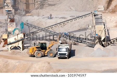 processing plant stones and excavator loading dumper truck - stock photo