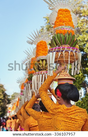 Procession of beautiful Balinese women in traditional costumes - sarong, carry offering on heads for Hindu ceremony. Arts festival, culture of Bali island and Indonesia people, Asian travel background - stock photo