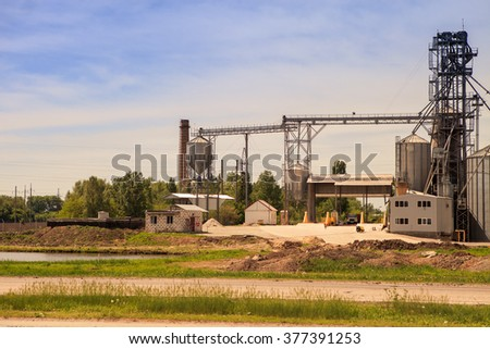 production yard with lift and machinery of modern silo in countryside near green trees - stock photo
