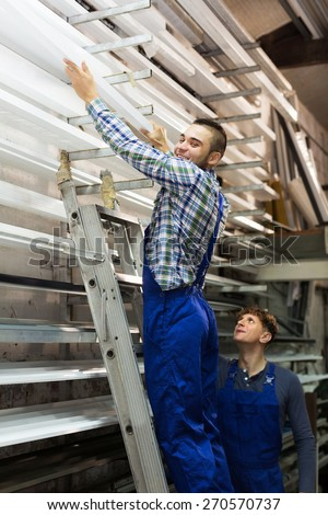 Production young workers in uniform with different PVC window profiles  - stock photo