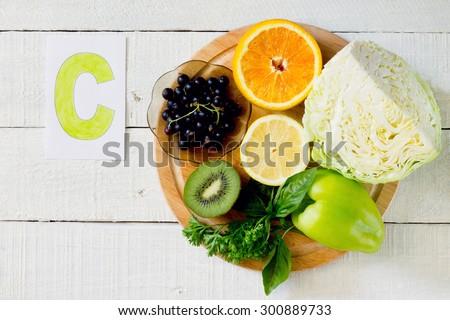 Products containing Vitamin C: orange, kiwi, lemon, black currant, sweet peppers, cabbage, parsley, basil - stock photo