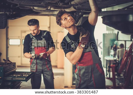 Profecional car  mechanics  working under lifted car in auto repair service. - stock photo