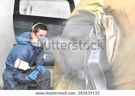 Profesional car body repair, Painting side panel. - stock photo