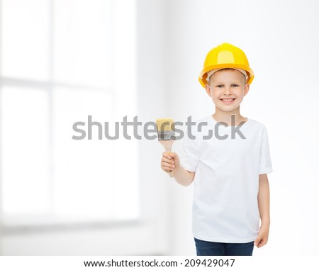 profession, future, childhood and people concept - smiling little boy in protective helmet with paint brush - stock photo