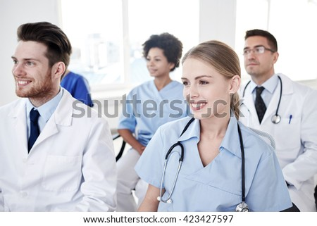 profession, medical education, health care, people and medicine concept - group of happy doctors on seminar in lecture hall at hospital - stock photo