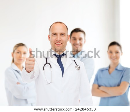 profession, teamwork, gesture and medicine concept - smiling male doctor with stethoscope in coat over group of medics showing thumbs up - stock photo