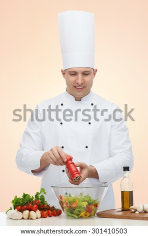 profession, vegetarian, food and people concept - happy male chef cooking and seasoning vegetable salad over beige background - stock photo