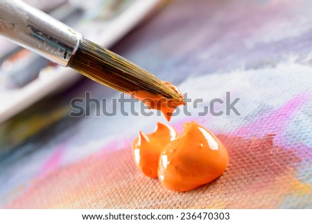 Professional acrylics orange paint on canvas and loaded brush - stock photo