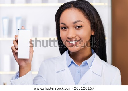 Professional advice. Beautiful young African woman in lab coat holding container with some medicine and smiling while standing in drugstore  - stock photo
