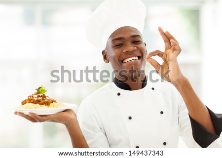 professional African chef holding spaghetti dish and making delicious hand sign - stock photo