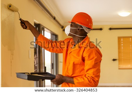 professional african construction worker painting the wall - stock photo