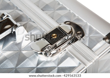 Professional aluminum makeup box lock closeup isolated at white background. Make up case for professional make-up artist. Beautician tools silver metal suticase. - stock photo