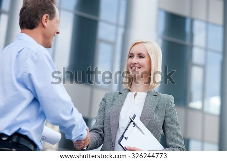 Professional architect and businesswoman are making handshake. They are standing near building and looking at each other with joy. The woman is holding documents. They are smiling - stock photo
