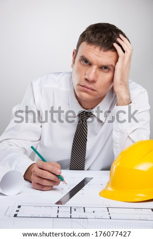 professional architect working with plan and thinking. man in white shirt sitting holding head - stock photo