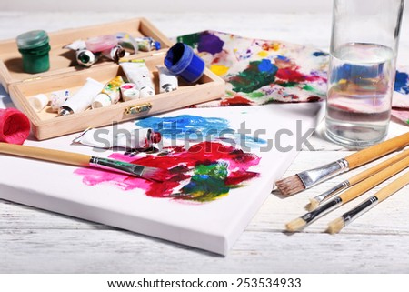 Professional art materials on color wooden background - stock photo