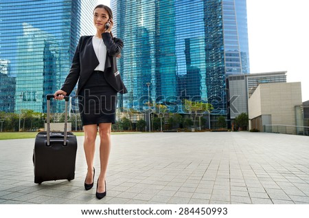 professional asian chinese travel business woman pulling suitcase bag walking along sidewalk on mobile phone outdoors in urban city - stock photo