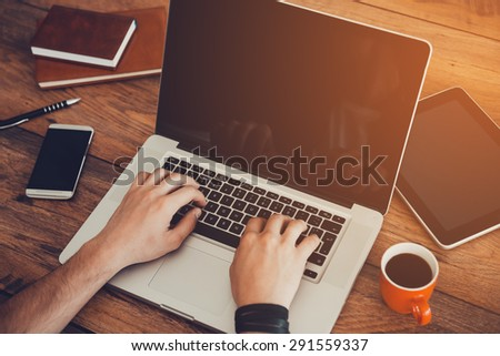 Professional at work. Top view ofman working on laptop while sitting at his working place  - stock photo