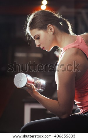 Professional athletic woman pumping up muscles with dumbbells in gym interior. Strong woman crossfit workout with dumbbell in gym, biceps exercise closeup. - stock photo