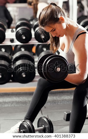 Professional athletic woman pumping up muscules with big heavy dumbbells in gym interior. Strong woman crossfit workout with dumbbell in gym, biceps exercise closeup. - stock photo