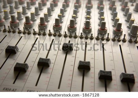 Professional audio mixing board with multiple channel faders and adjusting knobs - stock photo
