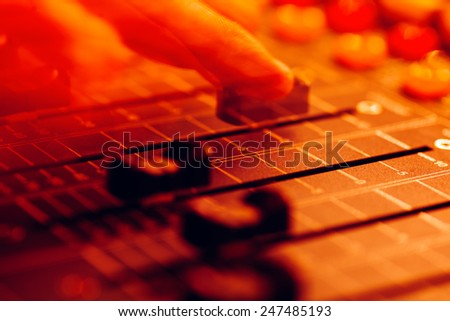 Professional audio mixing console with faders and adjusting knobs - radio / TV broadcasting,motion abstraction in colorful Light Show Concert - stock photo