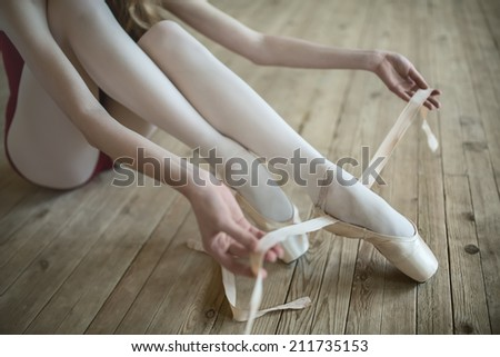 Professional ballerina putting on her ballet shoes. - stock photo