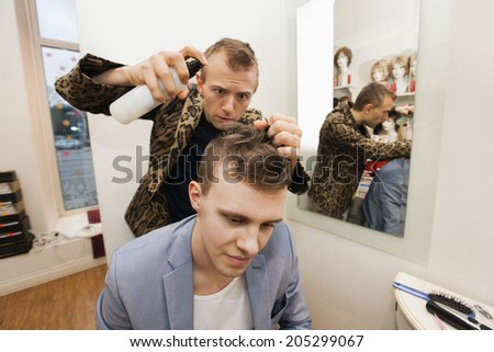 Professional barber using hairspray on male customer in shop - stock photo