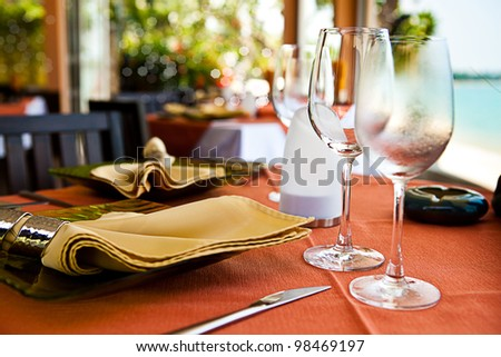 Professional beach restaurant serving with glasses and plates - stock photo