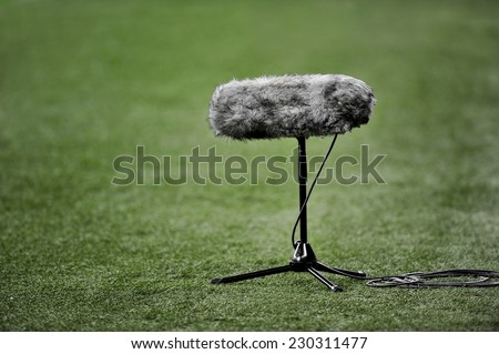 Professional boom microphone for live sport broadcasting on soccer field - stock photo