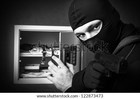 Professional burglar in black mask opened a small safe, holding hand gun and aiming - stock photo
