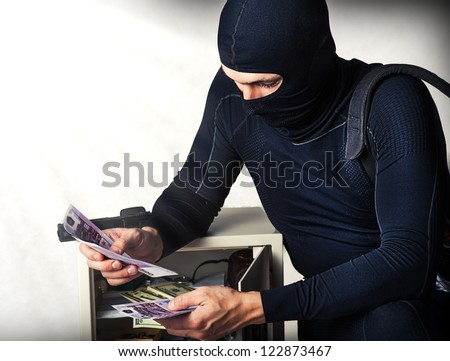 Professional burglar in black ski mask  opened a small safe, holding a lot of money - stock photo