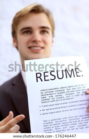 Professional Business Man Job Applicant Smiling Holding Resume Trying to Get Hired  - stock photo