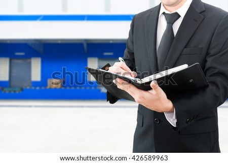 Professional businessman booking with blurred distribution warehouse background, industrial business concept - stock photo