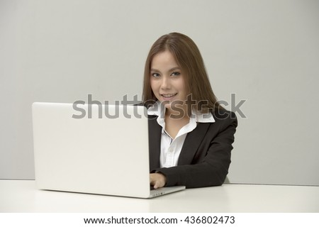 professional businesswoman sitting in front of laptop at her desk in an office while looking at camera and smiling. - stock photo