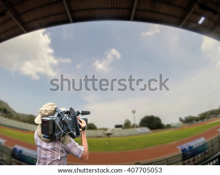 Professional cameraman and Video camera operator working in stadium and Running Trace, soccer field grass Goal at the stadium Soccer field - stock photo