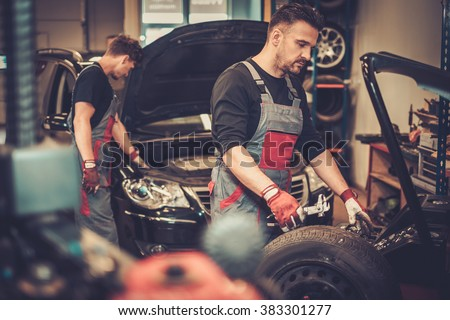 Professional car  mechanic balancing car wheel on balancer in auto repair service. - stock photo