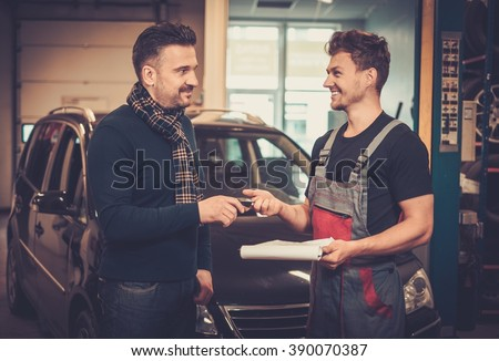 Professional car mechanic giving client keys to his repaired car in auto repair service. - stock photo